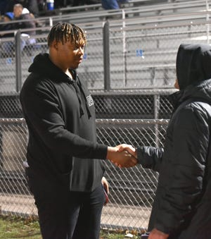Former Plymouth Wildcat and current NFL player with the Cincinnatti Bengals Michael Jordan greets a fan on the sidelines of the Wildcats' Nov. 1 playoff game.