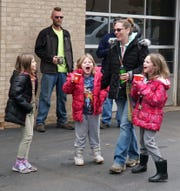 Sarina Carr, right, with her daughters Sierra, 7, and Savannah, 9, react to learning they've be awarded a Toyota Rav4 by Milford's Downtown Garage on Nov. 2.