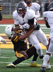 UofD Jesuit's Dorian Mausi is brought down by Raider Andrew Dooley.,