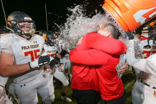 Palm Desert football coach Shane McComb gets a cold shower to celebrate after winning the school's second consecutive Desert Empire League title.