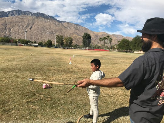 Brandon Duran, a Santa Rosa Rancheria Tachi-Yokut tribal member, shows a boy how to use a rabbit stick at the Kewet Learning Day and Market on Nov. 2, 2019.
