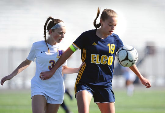Elco's Natalie Swingholm (19) holds back B-S's Bry McBeth (3) during first half action.