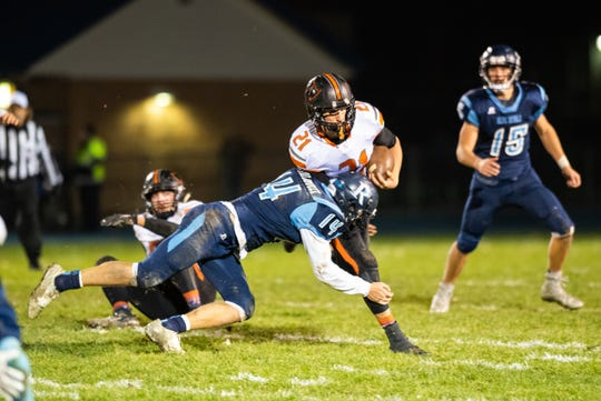 Almont running back Mason Smith (21) is stopped by Richmond's Matt Bartolomucci as he runs with the football  during their MHSAA Division 5 district playoff match Friday, Nov. 1, 2019, at Richmond High School.