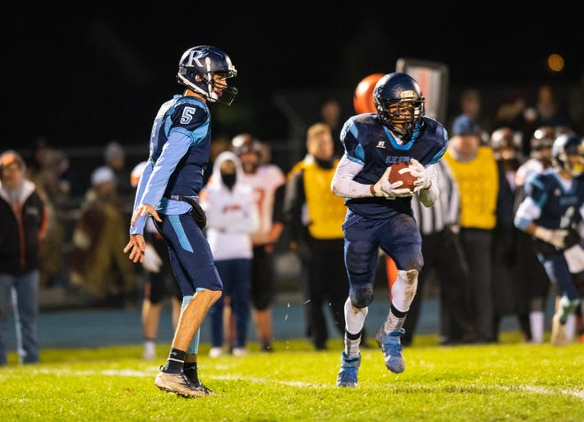 Richmond quarterback Brandon Schorman (5) hands the football off to Derek Snyder  during their MHSAA Division 5 district playoff match against Almont Friday, Nov. 1, 2019, at Richmond High School.