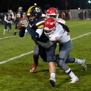 Port Huron Northern's Theo Ellis is tackled by two Port Huron Big Reds after a short pass during their football game Friday Nov. 1 at Memorial Stadium in Port Huron.
