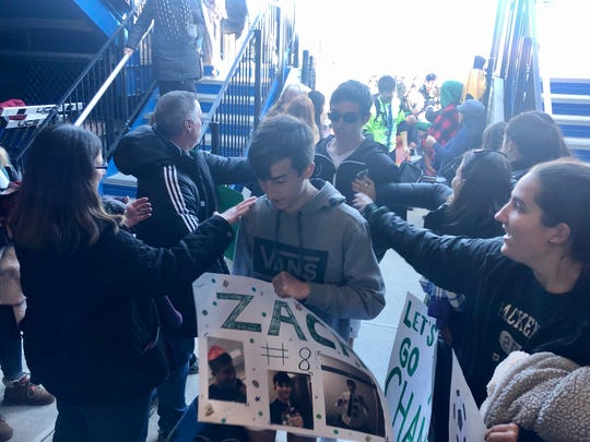 Zach Foroglou (front) and the Spackenkill boys soccer team is greeted by fans as the players leave the field after the Section 9 Class B final on Saturday.