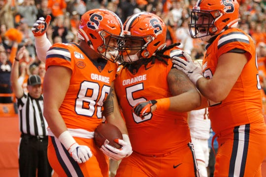 Syracuse's Aaron Hackett, left, celebrates with teammates Chris Elmore, center, and Carlos Vettorello, right, after scoring a touchdown during the first quarter of an NCAA college football game against Boston College in Syracuse, N.Y., Saturday, Nov. 2, 2019.