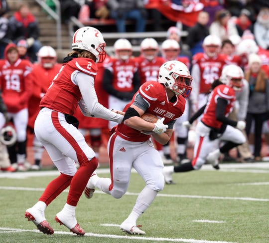 Johnnies quarterback Jackson Erdmann hands the ball off to Henry Trost Saturday, Nov. 2, 2019, at Clemens Stadium.