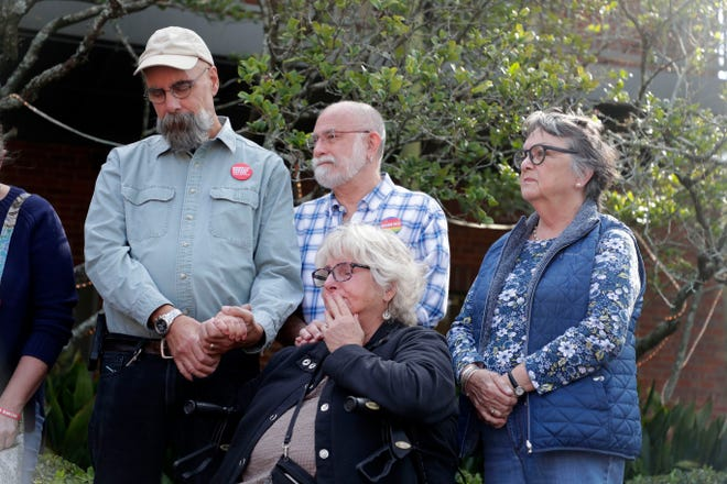 Neighbors, Doug Hahn, left, Ken Lux, Nancy Bivens, and Kim Maddox pause for a moment of silence during a memorial service at Betton Place honoring the lives that were lost last year during a fatal shooting at Hot Yoga.
