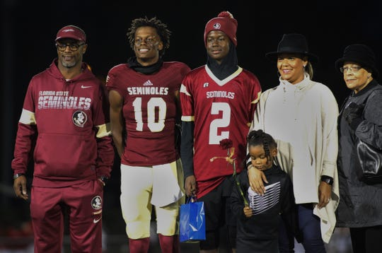 Florida High senior quarterback Willie Taggart Jr., with father Willie Taggart Sr., next to him, stands with his family for senior night as Florida High beat Leon 47-10 on Nov. 1, 2019.
