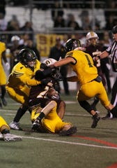 Simi Valley's Ranell White is taken down by Royal's Alberto Polanco (from left), Tanner Mactague and Nick Torres during the first quarter of Friday night's game. Simi Valley won, 21-0.
