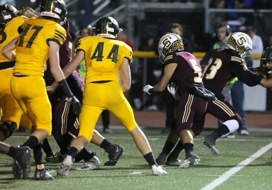 Simi Valley's Elijah Leiva finds an opening in Royal's defensive line to score the Pioneers' first touchdown in the third quarter of Friday night's game. Simi Valley won, 21-0.