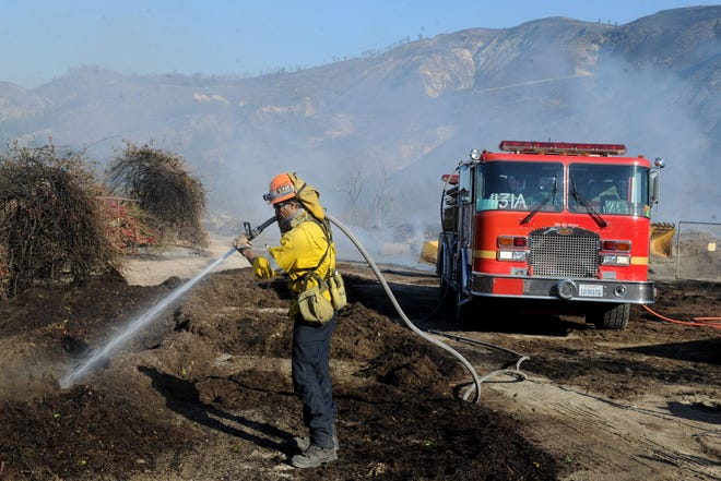 A firefighter works Friday to counter the Maria Fire, which broke out on Halloween night atop South Mountain.