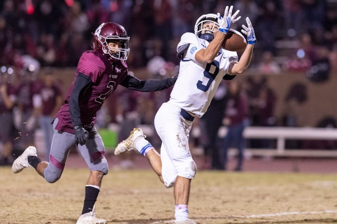 Redwood's Christian Roldan takes a pass ahead of Mt. Whitney's Josue Cisneros in the annual Cowhide rivalry game on Friday, November 1, 2019.