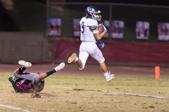 Redwood's Christian Roldan scores on a pass ahead of Mt. Whitney's Josue Cisneros in the annual Cowhide rivalry game on Friday, November 1, 2019.