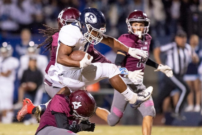 Redwood's James Richardson leaps over Mt. Whitney defenders in the annual Cowhide rivalry game on Friday, November 1, 2019.