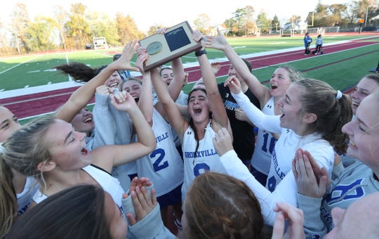 Bronxville's Sunday Ladas (8), center,  hoists the Section 1 plaque with teammates after defeating North Salem 2-0 in the Section 1 Class C field hockey championship game at Nyack High School in Nyack on Saturday, November 2, 2019.