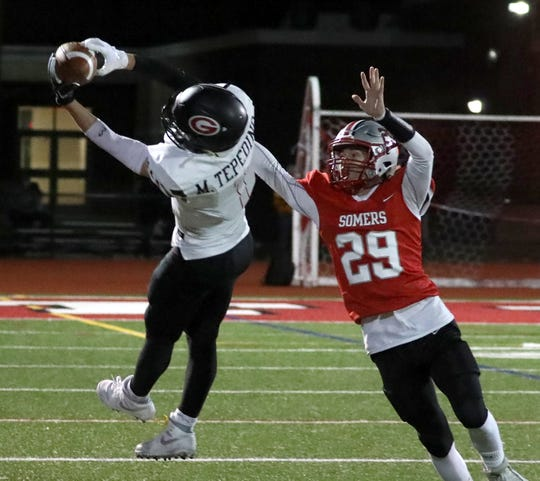 Rye's Matthew Tepidino catches a pass under pressure from Somers' Nate Rosenzweig during their Class A semifinal at Somers Nov. 1, 2019. Rye won 28-20.