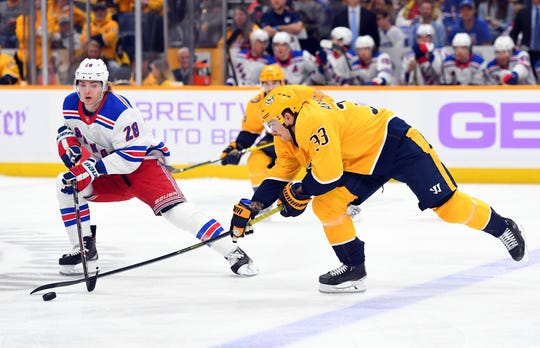 Nov 2, 2019; Nashville, TN, USA; Nashville Predators left wing Viktor Arvidsson (33) battles for the puck against New York Rangers center Lias Andersson (28) during the first period at Bridgestone Arena. Mandatory Credit: Christopher Hanewinckel-USA TODAY Sports
