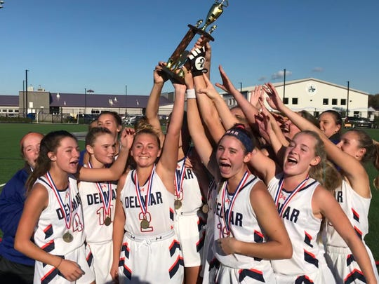 Delmar's field hockey team holds up the Henlopen Athletic Conference championship trophy Saturday, November 2, at Sussex Academy in Georgetown.