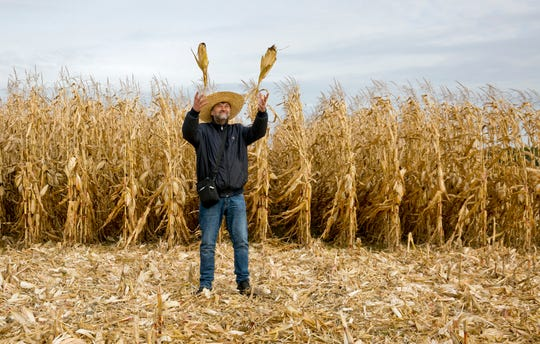 In this Oct. 12, 2019, photo, Serhii Halusyn, a farmer who leases land from people in the village of Nebelytsia, Ukraine, plays with ears of corn as speaks with The Associated Press. Most of Ukraine's rich farmland is carved up into small plots owned by about 7 million people. They are forbidden by law from selling it, although Ukraine's new president wants to change that.