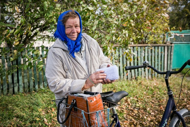In this Oct. 12, 2019, photo, Tetiana Petrovych, a postmistress, speaks to The Associated Press as she delivers the mail on her bicycle, in the village of Nebelytsia, Ukraine. Most of Ukraine's rich farmland is carved up into small plots owned by about 7 million people, like Petrovych. They are banned from selling it, although the country's new president wants to open the land market.