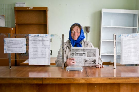 In this Oct. 12, 2019, photo, Tetiana Petrovych, a postmistress in Nebelytsia village, Ukraine, poses for a photo during an interview with The Associated Press. Most of Ukraine's rich farmland is carved up into small plots owned by about 7 million people, like Petrovych. They are forbidden by law from selling it, although Ukraine's new president wants to change that.