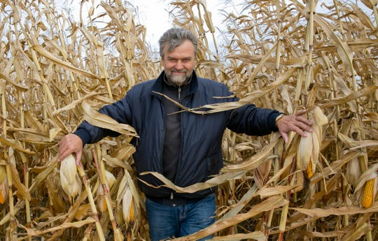 In this Oct. 12, 2019, photo, Serhii Halusyn, a farmer who leases land from people in the village, speaks with The Associated Press while standing in a corn field in the village of Nebelytsia, Ukraine. Most of Ukraine's rich farmland is carved up into small plots owned by about 7 million people. They are banned from selling it, although the country's new president wants to open the land market.