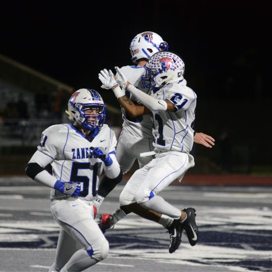 Senior kicker Gabe Dolen is congratulated by teammate Julius Murphy after booting a 36-yard field goal during Zanesville's 52-28 win against host Marietta on Friday night at Don Drumm Stadium.