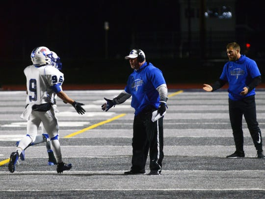 Head coach Chad Grandstaff congratulates Jordan Martin after scoring a touchdown during Zanesville's 52-28 win against host Marietta last Friday at Don Drumm Stadium. The Blue Devils will play at Granville on Friday night in the first round of the Division III, Region 11 playoffs.
