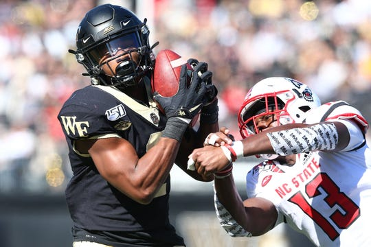 Wake Forest Demon Deacons wide receiver Kendall Hinton catches a pass against North Carolina State Wolfpack linebacker Tyler Baker-Williams during the second quarter at BB&T Field in Winston-Salem, N.C.