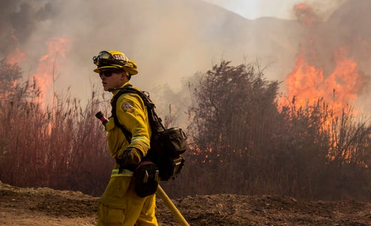 A Cal Fire firefighter works on the Maria blaze in the hills near Ventura, Calif., on Nov. 1, 2019.