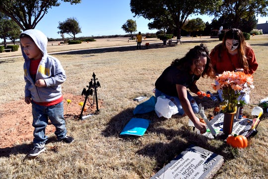 Sisters Noehmi Rodriguez (center) and Angelica Rodriguez tend the grave of Angelica's son Karson Angel Rodriguez Wilson who died April 6, 2017. The family was at Elliott-Hamil Funeral Homes and Garden of Memories Cemetery for Dia de los Muertos with Luis Patino, 2, (left) and Julio Abrego, 7, Saturday.