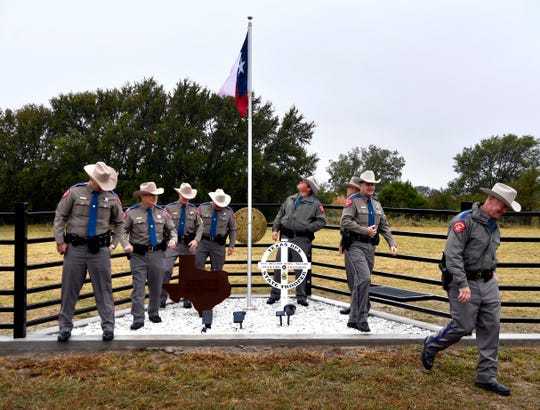 """Texas Department of Public Safety troopers step away after taking a group picture at the roadside memorial for Sgt. William """"Karl"""" Keesee Tuesday. The display is on private land near the site were Keesee died on duty exactly four years earlier in 2015. The stretch of U.S. 84 here has been renamed in his honor."""