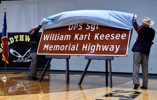 """Lt.Richard Villanueva (left) and Sgt. Chad Gossett unveil Tuesday one of the signs that will be used to designate a portion of U.S. 84 through Mills County in honor of William """"Karl"""" Keesee."""