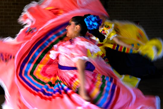 Ariana Rodriguez twirls as folklorico dancers from St. Vincent Pallotti Catholic Church perform Saturday at Elliott-Hamil Funeral Homes and Garden of Memories Cemetery. This was the cemetery's first Dia de los Muertos celebration.