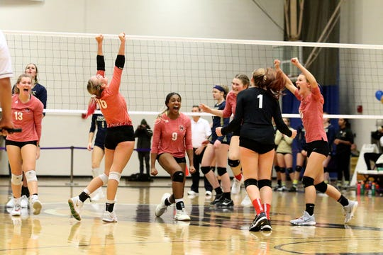CVU's Mekkena Boyd (center) and her teammates react as they pull to within 1 point of claiming the high school girls volleyball championship. The Redhawks went on to defeat top seeded Essex 3-2 at St. Michael's College on Saturday night.