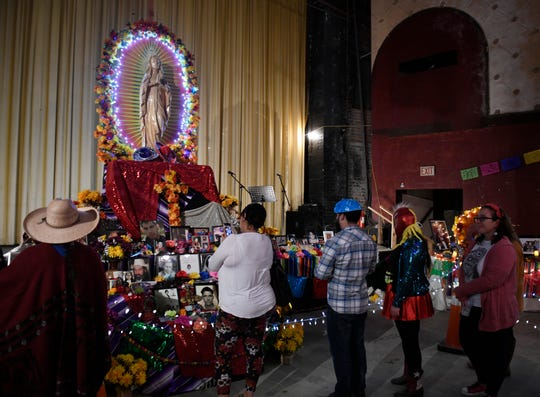 Attendees pass an Ofrenda at Dia de los Muertos Street Festival, Saturday, Nov. 2, 2019. Ofrendas are offering tables, filled with flowers, fruit and photos, to pay tribute to deceased family members.