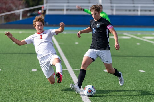 Wyoming senior Sam Renggli attempts to advance the ball while a Tipp City defender comes in with a slide tackle.