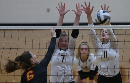 Roger Bacon players Abbie Schneider (11) and Karly Niesen (7) get a block against Bishop Fenwick player Grace Dinkelaker (6) during their regional final, Saturday, Nov. 2, 2019.