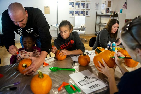 Children and adults decorate and carve pumpkins during an event hosted by staff members at Elizabeth Warren's campaign office in Indianola on Thursday, Oct. 24, 2019.