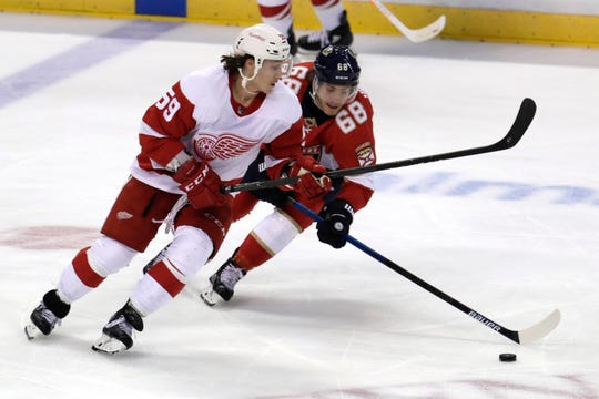 Detroit Red Wings left wing Tyler Bertuzzi and Florida Panthers center Mike Hoffman go for the puck during the third period Saturday, Nov. 2, 2019, in Sunrise, Fla.