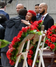 Monica Conyers hugs an unidentified man during the visitation.  At right is Carl Conyers, son of Monica and John Conyers, Jr.