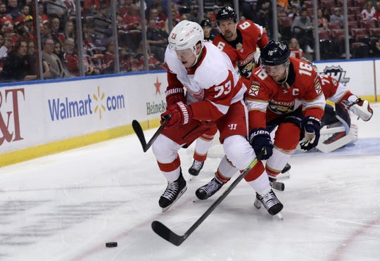 Detroit Red Wings left wing Adam Erne and Florida Panthers center Aleksander Barkov go for the puck Saturday night.