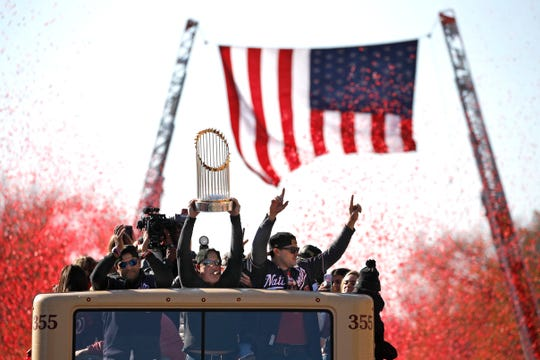 Washington Nationals general manager Mike Rizzo holds up the World Series trophy during a parade Saturday to celebrate the team's World Series baseball championship over the Houston Astros in Washington.