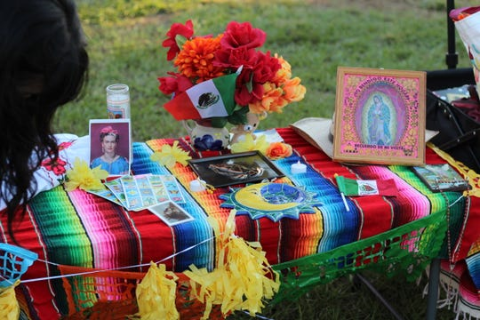 "Students create an ""ofrenda"" at the CDU Dia de los Muertos event on Landis Green."