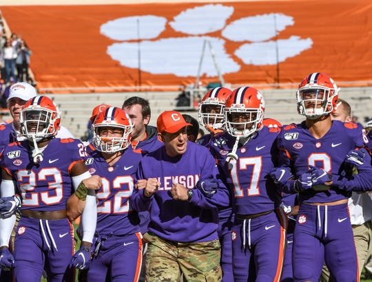 Clemson Head Coach Dabo Swinney arm in arm with wide receiver Will Swinney (22) and wide receiver Cornell Powell (17) before the game at Memorial Stadium in Clemson, South Carolina Saturday, November 2, 2019.