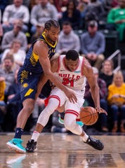 Chicago Bulls forward Thaddeus Young (21) works to regain control of the ball as he is defended by Indiana Pacers forward T.J. Warren, left, during the first half of an NBA basketball game in Indianapolis, Sunday, Nov. 3, 2019.