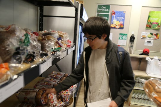 Kurt Lui looks through bread at the Panther Pantry at Tompkins Cortland Community College.