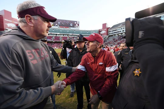 Mississippi State coach Joe Moorhead, left, shakes hands with Arkansas coach Chad Morris after Saturday's game.